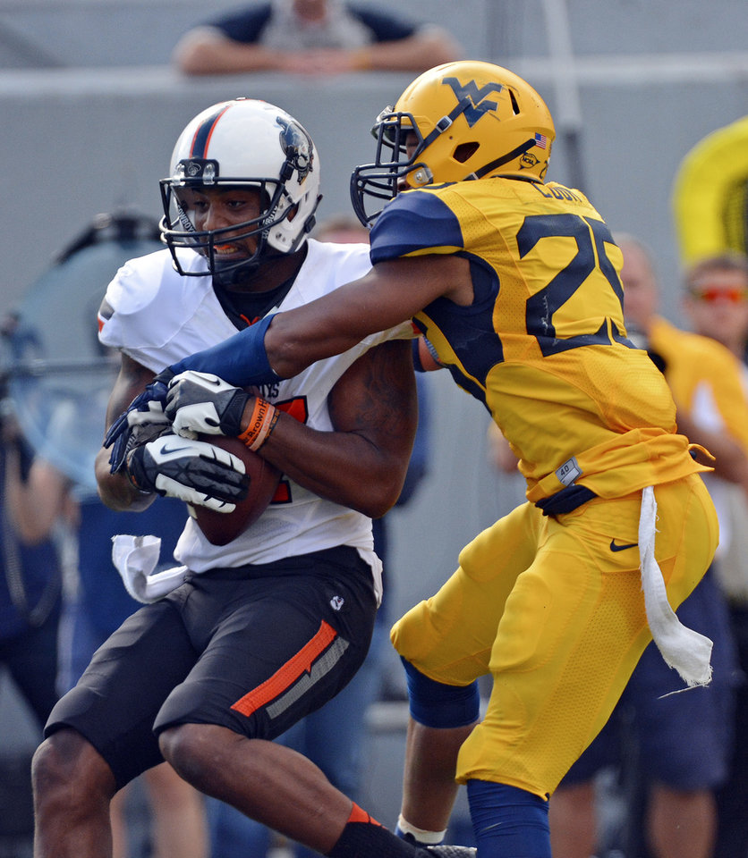 Photo - Oklahoma State receiver Tracy Moore (87) is tackled by West Virginia defender Darwin Cook (25) in the third quarter of an NCAA college football game in Morgantown, W.Va., on Saturday, Sept. 28, 2013. (AP Photo/Tyler Evert) ORG XMIT: WVTE301