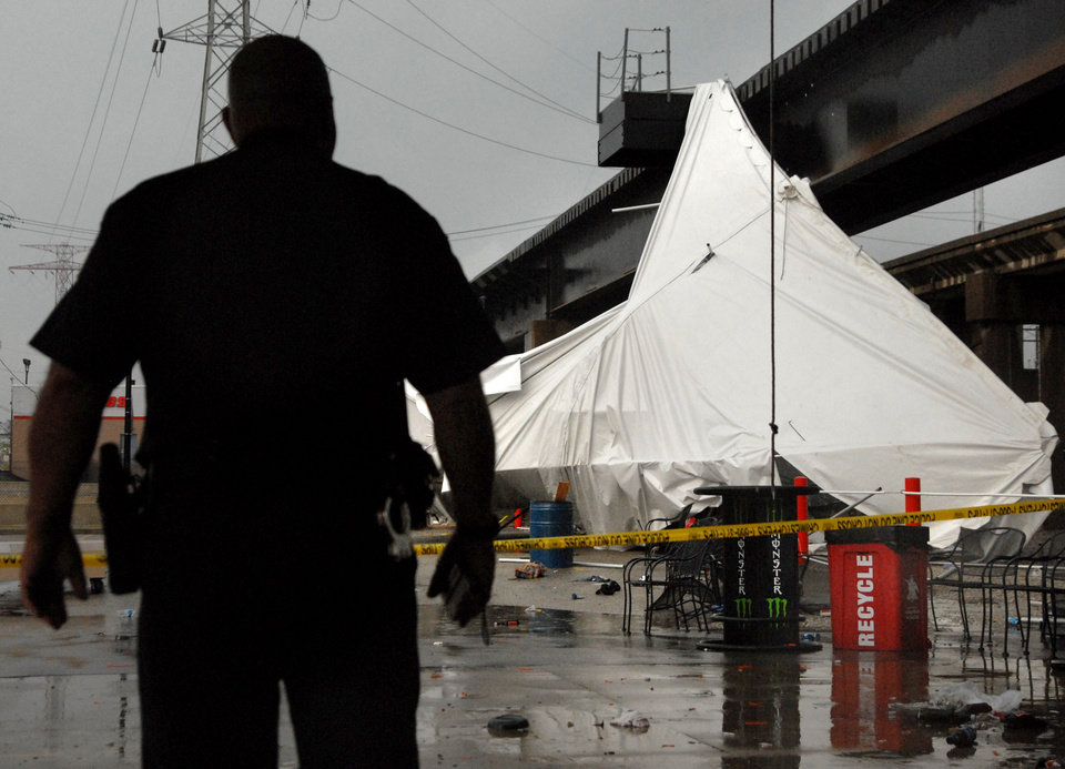 Photo -   An officer from the Terminal Railroad Police Department surveys a party tent from Kilroy's Sports Bar in St. Louis as it rests against a railroad trestle near the bar after storm winds blew through the area following a baseball game between the St. Louis Cardinals and Milwaukee Brewers at nearby Busch Stadium Saturday, April 28, 2012. One person died Saturday and more than a dozen were taken to a hospital with injuries after high winds blew over a beer tent near Busch Stadium in St. Louis. (AP Photo/Sid Hastings)