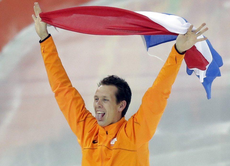 Photo - Stefan Groothuis of the Netherlands holds his national flag and celebrates after winning the gold in the men's 1,000-meter speedskating race at the Adler Arena Skating Center at the 2014 Winter Olympics in Sochi, Russia, Wednesday, Feb. 12, 2014. (AP Photo/David J. Phillip, File)