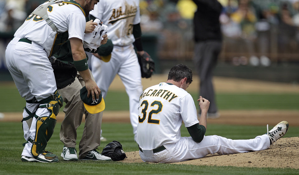Photo -   Oakland Athletics catcher Derek Norris, left, comes to the aid of pitcher Brandon McCarthy (32) who was hit in the head by a ball hit by Los Angeles Angels' Erick Aybar in the fourth inning of a baseball game on Wednesday, Sept. 5, 2012, in Oakland, Calif. McCarhy left the game after the incident. (AP Photo/Ben Margot)