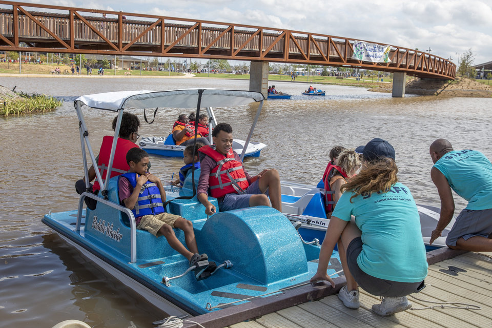 Photo - A family prepares to ride a paddle boat during the grand opening weekend of Scissortail Park in Oklahoma City, Sunday, Sept. 29, 2019. (Alonzo Adams for The Oklahoman)