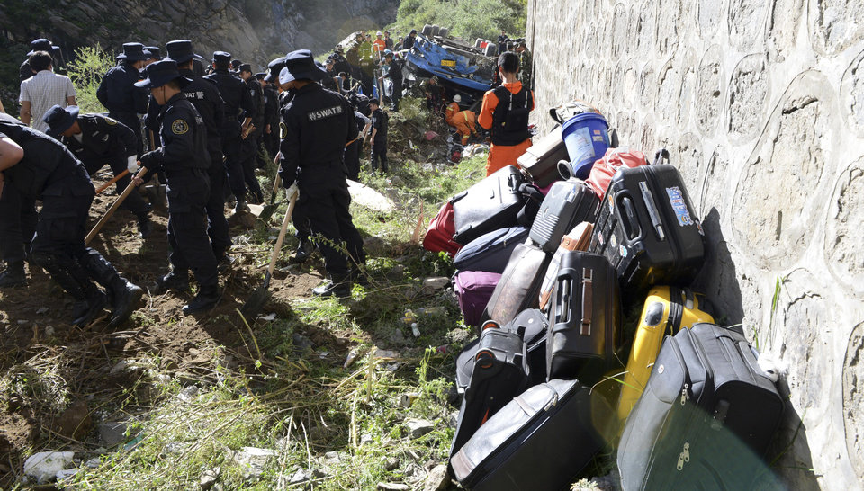 Photo - In this photo released by China's Xinhua News Agency, suitcases of tour bus passengers are piled up as rescuers work near an overturned bus after it fell off a 10-meter (30-foot) cliff in Nyemo County, southwest China's mountainous region of Tibet Saturday, Aug. 9, 2014. Xinhua reported the bus carrying about 40 people careened after it crashed in a pileup involving a sports utility vehicle and a pickup truck on a state road. Casualty details were not immediately known. (AP Photo/Xinhua, Chogo) NO SALES