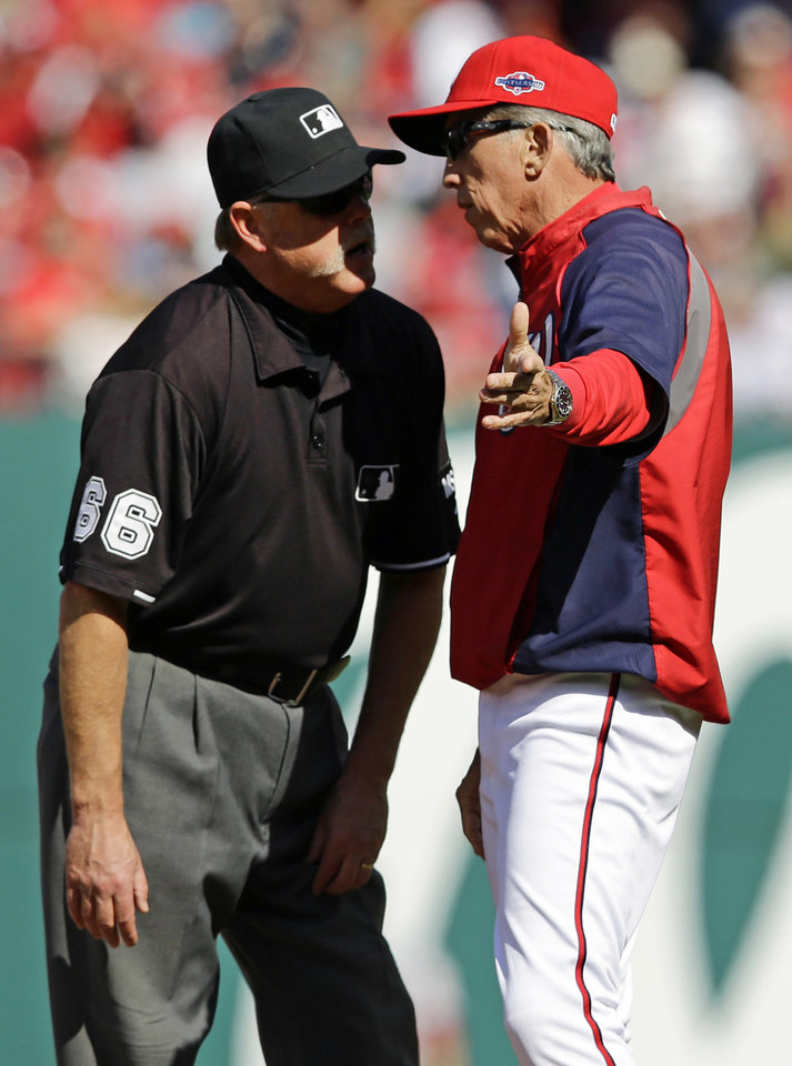 Photo -   Washington Nationals manager Davey Johnson, right, protests a call with first base umpire Jim Joyce after Washington's Danny Espinosa was called out at first base in the first inning of Game 3 of the National League division baseball series on Wednesday, Oct. 10, 2012, in Washington. (AP Photo/Alex Brandon)