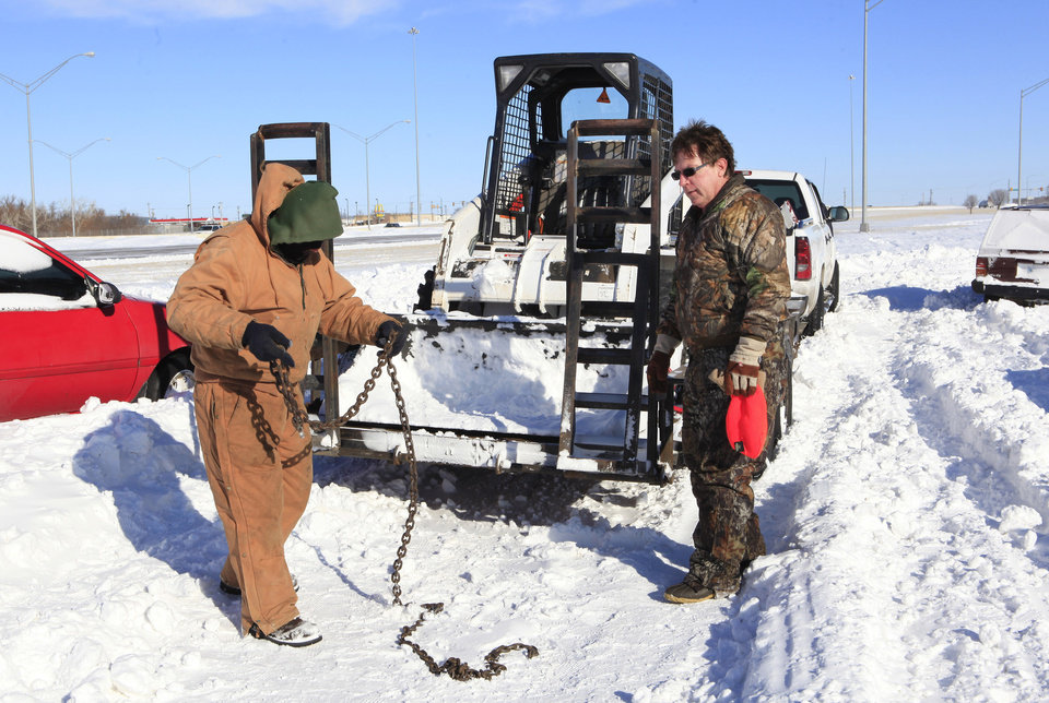 Photo - Curt Pointer, right, Oklahoma City, and Lalo Torrez use a chain to tow a vehicle after it got stuck on the Britton Road northbound off ramp of the Broadway Extension Wednesday, Feb. 2, 2011. Seven vehicles were stuck there preventing snow plows from clearing the area of large snow drifts. Photo by Paul B. Southerland, The Oklahoman