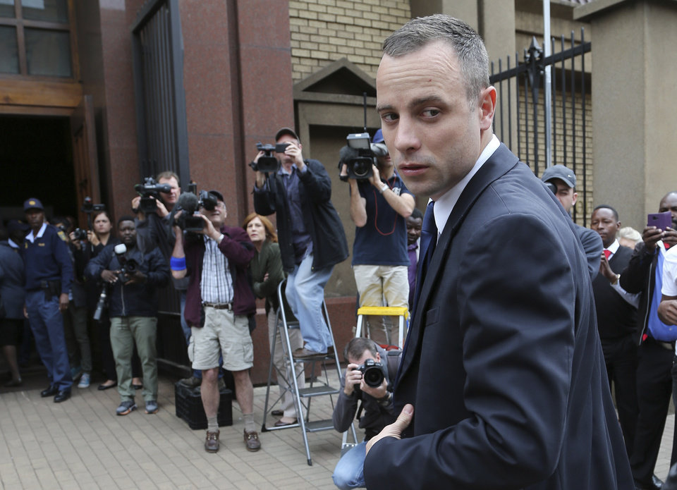 Photo - Oscar Pistorius looks back as he arrives at the high court in Pretoria, South Africa, Tuesday, May 6, 2014. Using witness accounts of a panicked nighttime phone call from Pistorius begging for help and his desperate pleas for Reeva Steenkamp to stay alive, the defense at his murder trial tried to reinforce its case Monday that the double-amputee Olympian fatally shot his girlfriend in a tragic error of judgment. (AP Photo/Themba Hadebe)