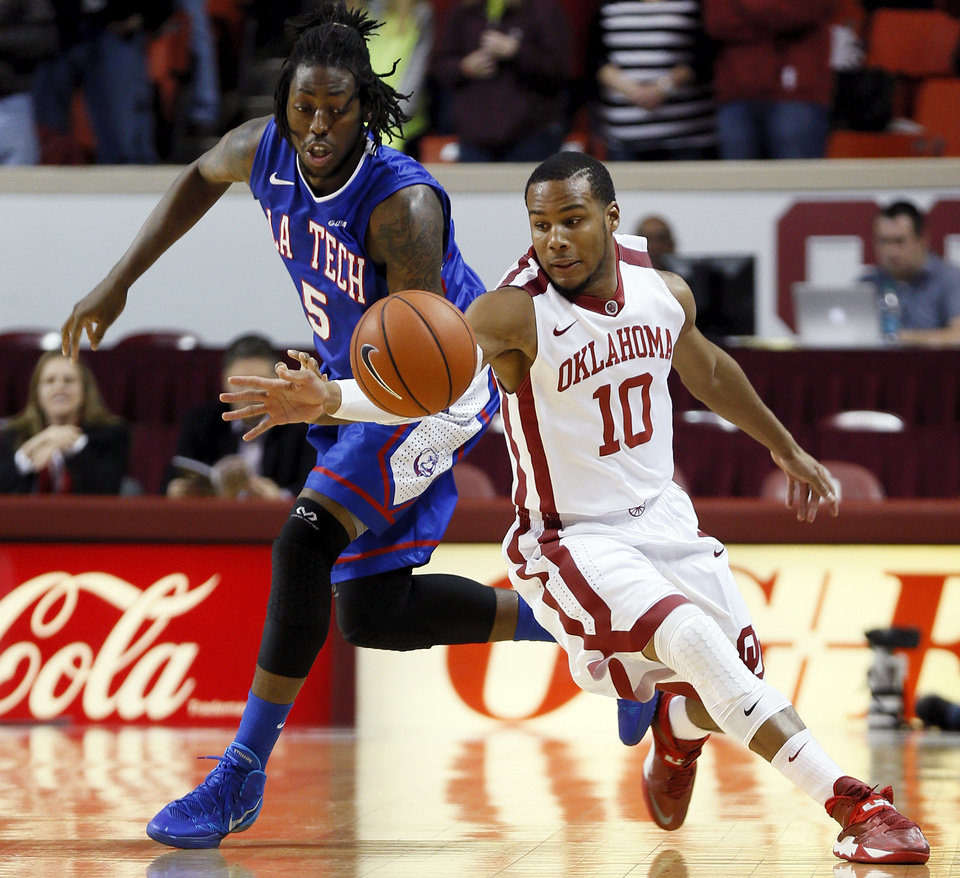 Oklahoma's Jordan Woodard (10) and Louisiana Tech's Chris Anderson (5) chase the ball during a men's college basketball game between the University of Oklahoma Sooners (OU) and the Louisiana Tech Bulldogs at Lloyd Noble Center in Norman, Okla.,  Monday, Dec. 30, 2013. Photo by Nate Billings, The Oklahoman