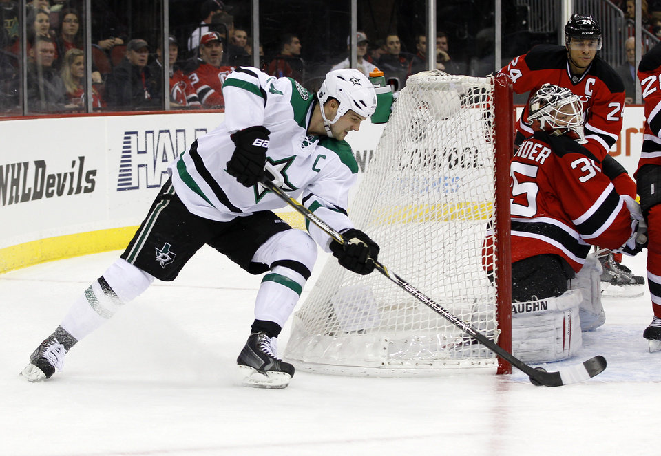 Photo - New Jersey Devils goalie Cory Schneider makes a save on a shot by Dallas Stars left wing Jamie Benn during the first period of an NHL hockey game Thursday, Jan. 9, 2014, in Newark, N.J. (AP Photo/Adam Hunger)