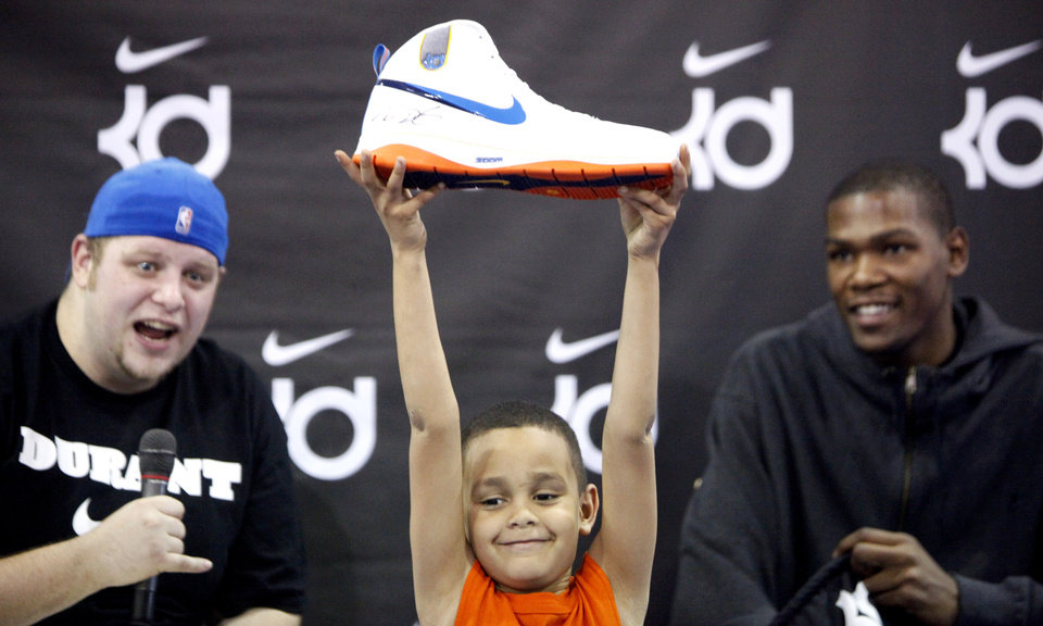 Photo - Camrin Jackson holds up his signed size 17 Kevin Durant shoe he won in a raffle at the Nike Clinic at the Salvation Army Boy and Girls  Club, Saturday, Feb. 7, 2009, in Oklahoma City.  Power 103.5 disc jockey J-Swick, left, and Oklahoma City Thunder player Kevin Durant look on in the background. PHOTO BY SARAH PHIPPS, THE OKLAHOMAN