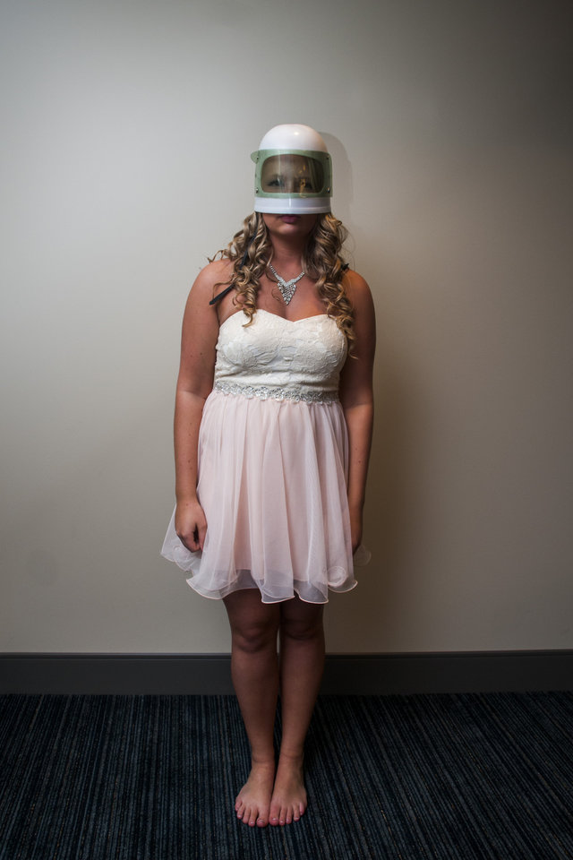Photo - Durand High School junior Madison Alander, 17, stands for a photo with a space helmet on her head at Michigan Stadium on the University of Michigan campus, Saturday, May 10, 2014, in Ann Arbor, Mich. The junior-senior prom for students at Durand High School was the first prom hosted by the 100,000-plus-seat football venue. The group took photos on the field, visited the locker rooms and had their dancing and dinner in the Jack Roth Stadium Club until midnight. (AP Photo/The Flint Journal, Jake May) LOCAL TV OUT; LOCAL INTERNET OUT