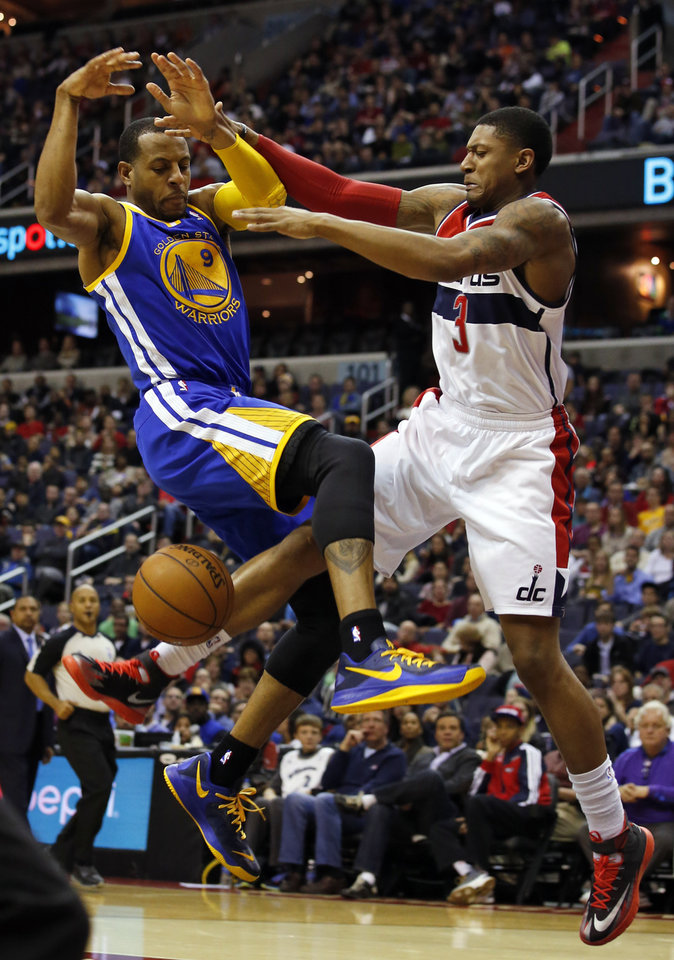 Photo - Golden State Warriors forward Andre Iguodala (9) is fouled by Washington Wizards guard Bradley Beal (3) in the first half of an NBA basketball game on Sunday, Jan. 5, 2014, in Washington. (AP Photo/Alex Brandon)