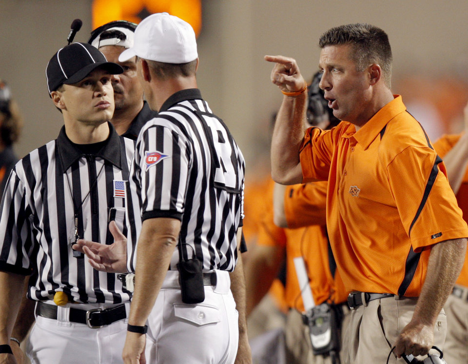 Photo - OSU head coach Mike Gundy argues a call during the college football game between the Oklahoma State University Cowboys (OSU) and the Troy University Trojans at Boone Pickens Stadium in Stillwater, Okla., Saturday, Sept. 11, 2010. Photo by Sarah Phipps, The Oklahoman