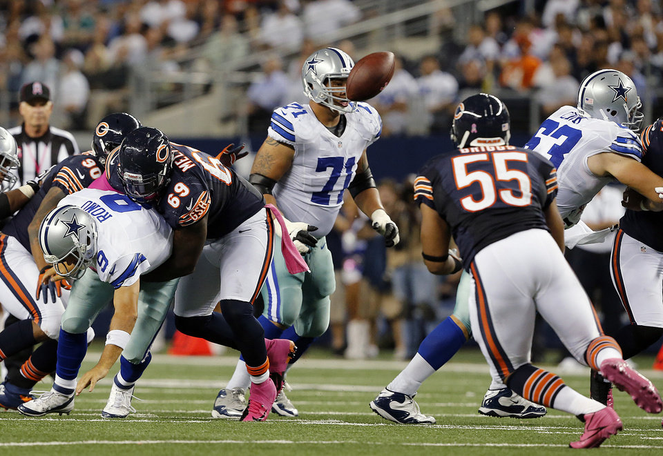 Chicago Bears outside linebacker Lance Briggs (55) intercepts the football as Dallas Cowboys quarterback Tony Romo (9) is sacked by Bears defensive tackle Henry Melton (69) during the second half of an NFL football game Monday, Oct. 1, 2012, in Arlington, Texas. The Bears won 34-18. (AP Photo/The Waco Tribune-Herald, Jose Yau)
