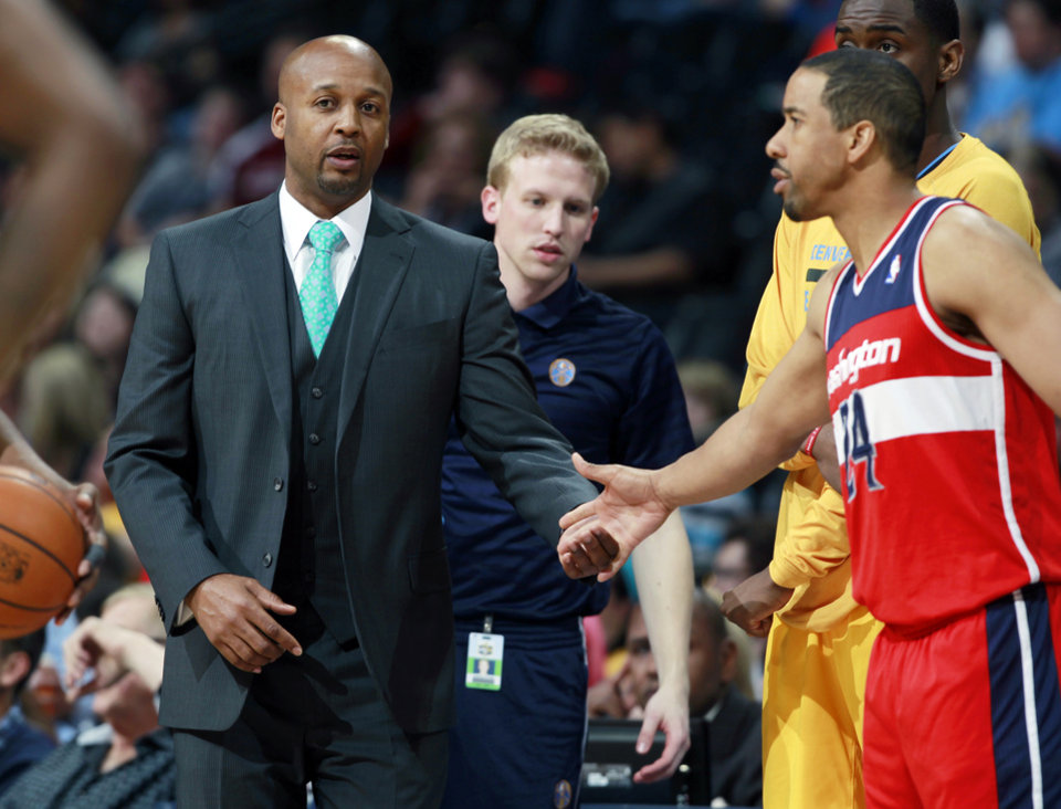 Photo - Denver Nuggets head coach Brian Shaw, left, greets Washington Wizards guard Andre Miller as he takes floor in the first quarter of an NBA basketball game on Sunday, March 23, 2014, in Denver. Shaw and Miller argued over playing time for Miller during a game on New Year's Day, which ended up in Miller being traded to Washington. (AP Photo/David Zalubowski)