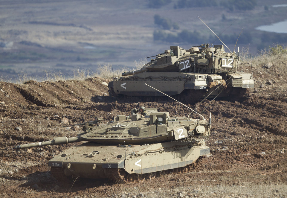 "Israeli tanks, one in position, the other getting into a firing position in the Israeli-controlled Golan Heights overlooking the Syrian village of Bariqa, Monday, Nov. 12, 2012. The Israeli military says ""Syrian mobile artillery"" was hit after responding to stray mortar fire from its northern neighbor. The incident marked the second straight day that Israel has responded to fire from Syria that does not appear to be aimed at Israeli targets, nonetheless Israel has promised a tough response if the fire continues. (AP Photo/Ariel Schalit)"
