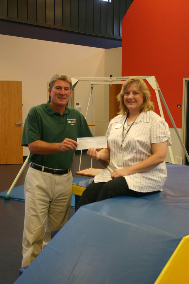 Helen Hubble, human resources manager for SITEL, (right) presents a check for $700 to Uwe von Schamann, director of development for the J. D. McCarty Center, on behalf of the 400 SITEL employees in Norman. Each quarter the SITEL employees select a non-profit organization to support through fundraising activities within the company. This donation will go to the McCarty Center's Camp ClapHans summer camp scholarship fund.<br/><b>Community Photo By:</b> Greg Gaston<br/><b>Submitted By:</b> Greg,