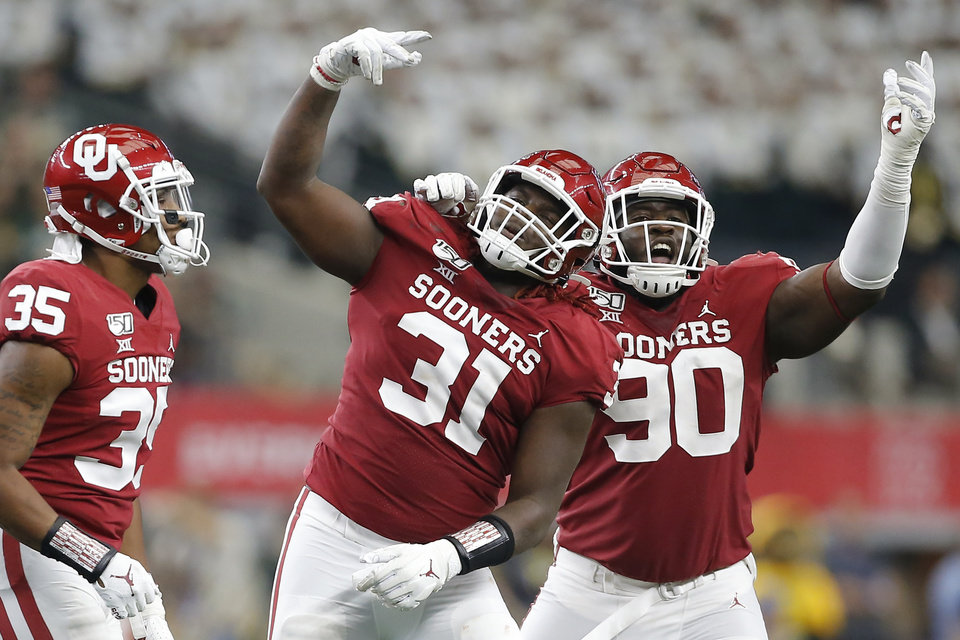 Photo - Oklahoma's Jalen Redmond (31) and Neville Gallimore (90) celebrate during the Big 12 Championship Game between the University of Oklahoma Sooners (OU) and the Baylor University Bears at AT&T Stadium in Arlington, Texas, Saturday, Dec. 7, 2019. Oklahoma won 30-23. [Bryan Terry/The Oklahoman]