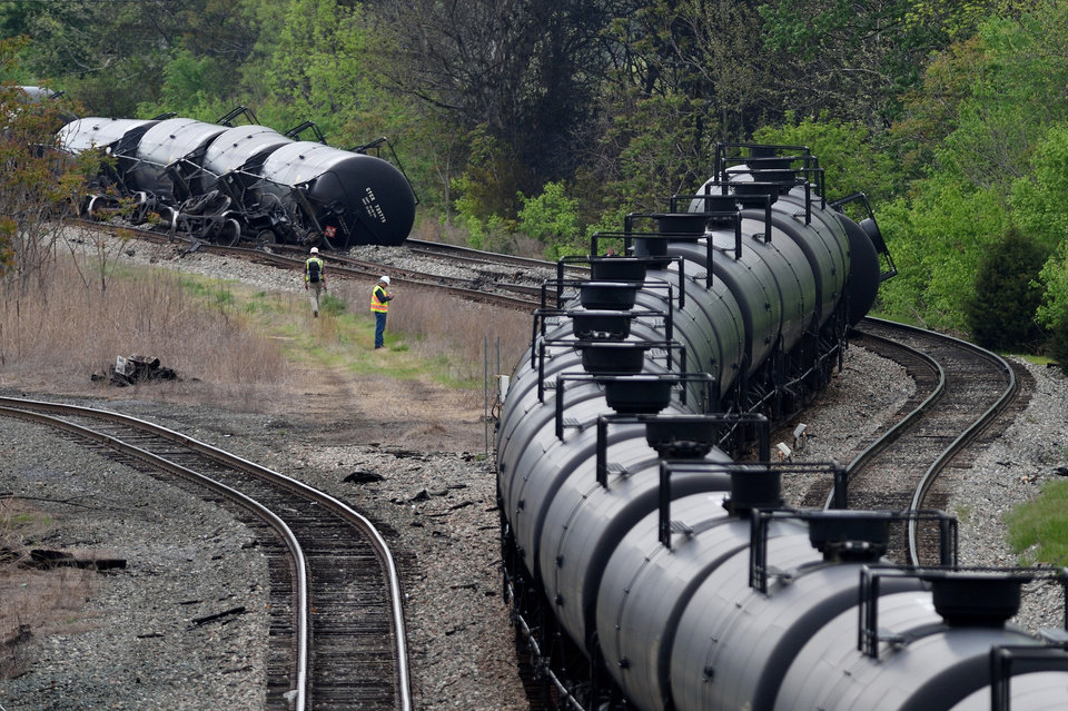 Photo -  Workers inspect the scene after several CSX tanker cars carrying crude oil derailed and caught fire Wednesday along the James River near downtown Lynchburg, Va. The area was evacuated for a time, but officials said there were no injuries. AP Photo   Parker Michels-Boyce -
