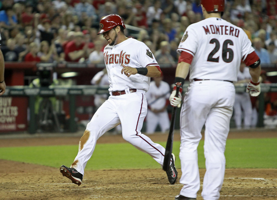 Photo - Arizona Diamondbacks' David Peralta, left, crosses the plate in front of teammate Miguel Montero as he scores on a wild pitch by Pittsburgh Pirates' Edinson Volquez during the fifth inning of a baseball game, Friday, Aug. 1, 2014, in Phoenix. (AP Photo/ Ralph Freso)