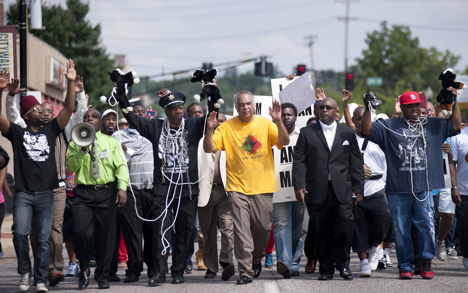 Photo - Protesters fill Florissant Road in downtown Ferguson, Mo. Monday, Aug. 11, 2014, marching along the closed street. The rally marched along the street in front of the town's police headquarters to protest the shooting of 18-year-old Michael Brown by Ferguson police officers on Saturday. (AP Photo/Sid Hastings)