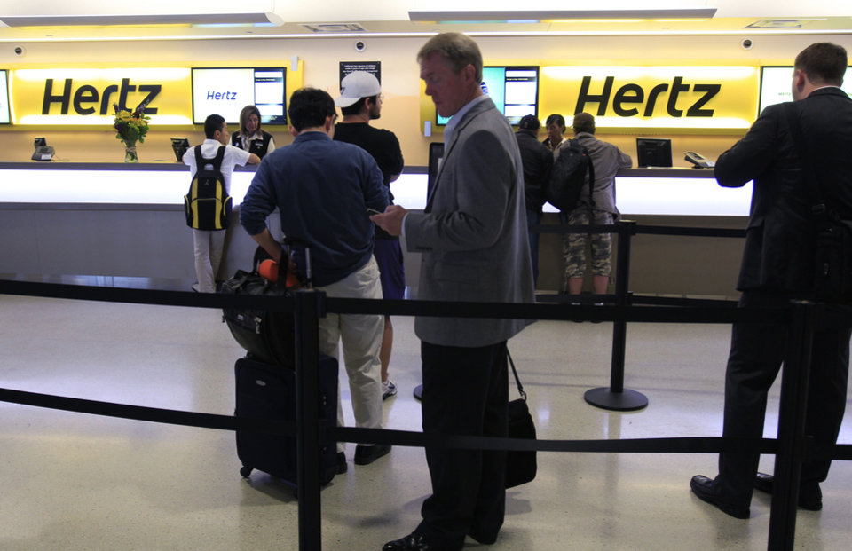 Photo - FILE - In this May 9, 2011 file photo, customers wait in line at a Hertz rental car counter at San Jose International Airport in San Jose, Calif. More than two years after its original bid, Hertz agreed Sunday, Aug. 26, 2012, to buy Dollar Thrifty Automotive Group Inc. for about $2.3 billion, giving it more ways to attract travelers and expand its international presence. It will also give the company a leg up against competition from an increasing number of smaller competitors. (AP Photo/Paul Sakuma, File) ORG XMIT: NY119