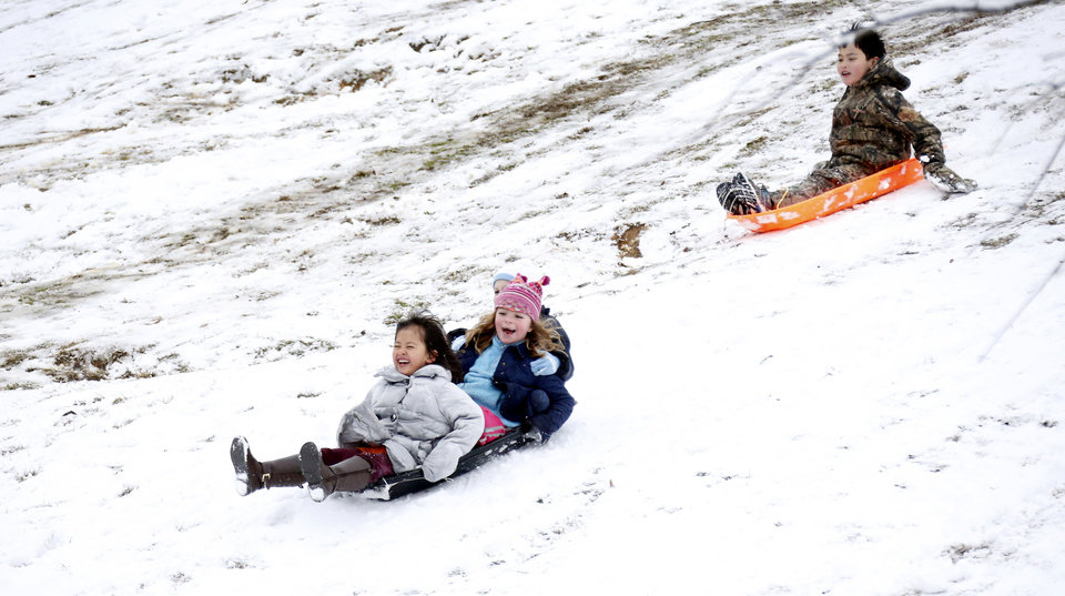 Photo - Children enjoy sledding down the hills in Avent  Park, Friday in Oxford, Miss., Jan. 22, 2016. The two inches of accumulated power was enough for many families who trekked to the park to take advantage of the long gentle slopes for their children to slide down. Although the snow ceased falling, temperatures are expected to drop in the afternoon making for hazardous driving in north Mississippi. (AP Photo/Rogelio V. Solis)