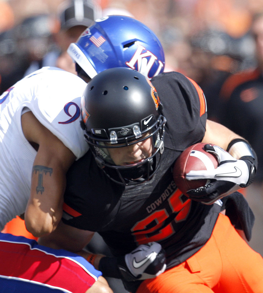 Photo - Oklahoma State's Josh Cooper (25) is tackled by Kansas' Keeston Terry (9)during the first half of the college football game between the Oklahoma State University Cowboys (OSU) and the University of Kansas Jayhawks (KU) at Boone Pickens Stadium in Stillwater, Okla., Saturday, Oct. 8, 2011. Photo by Sarah Phipps, The Oklahoman