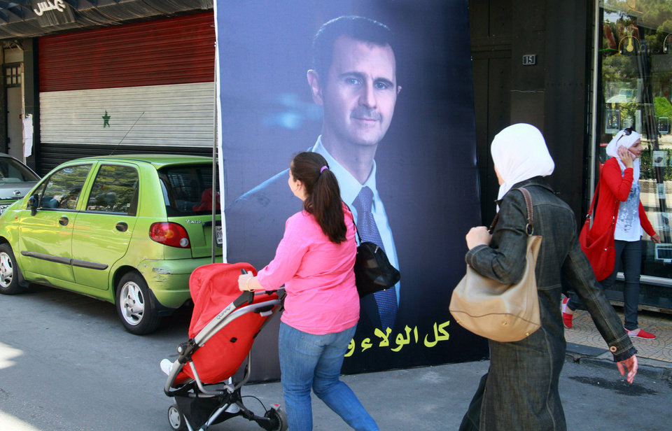 People walk by a campaign poster of the presidential elections for the incumbent President Bashar Assad in Damascus, Syria, Saturday, May 24, 2014. Assad\'s family has ruled Syria for more than 40 years. The June 3 vote will be the first time the family has faced challengers as opposed to a yes-or-no vote on their rule. (AP Photo)