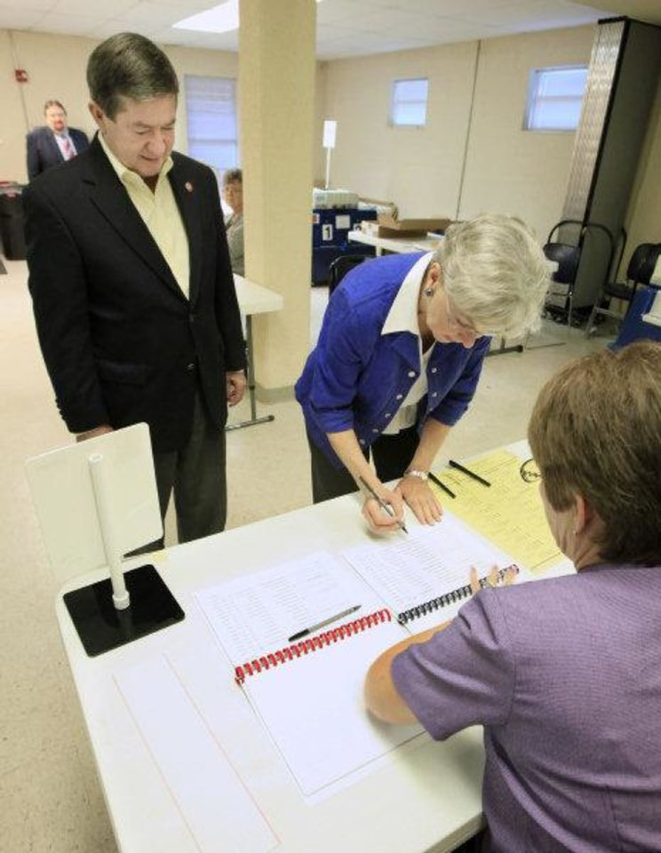 Attorney General Drew Edmondson, gubernatorial candidate and his wife Linda Edmondson sign in to vote at precinct 574 Sooner and Hefner roads, in northeast Oklahoma City Tuesday.  <strong>PAUL B. SOUTHERLAND - PAUL B. SOUTHERLAND</strong>