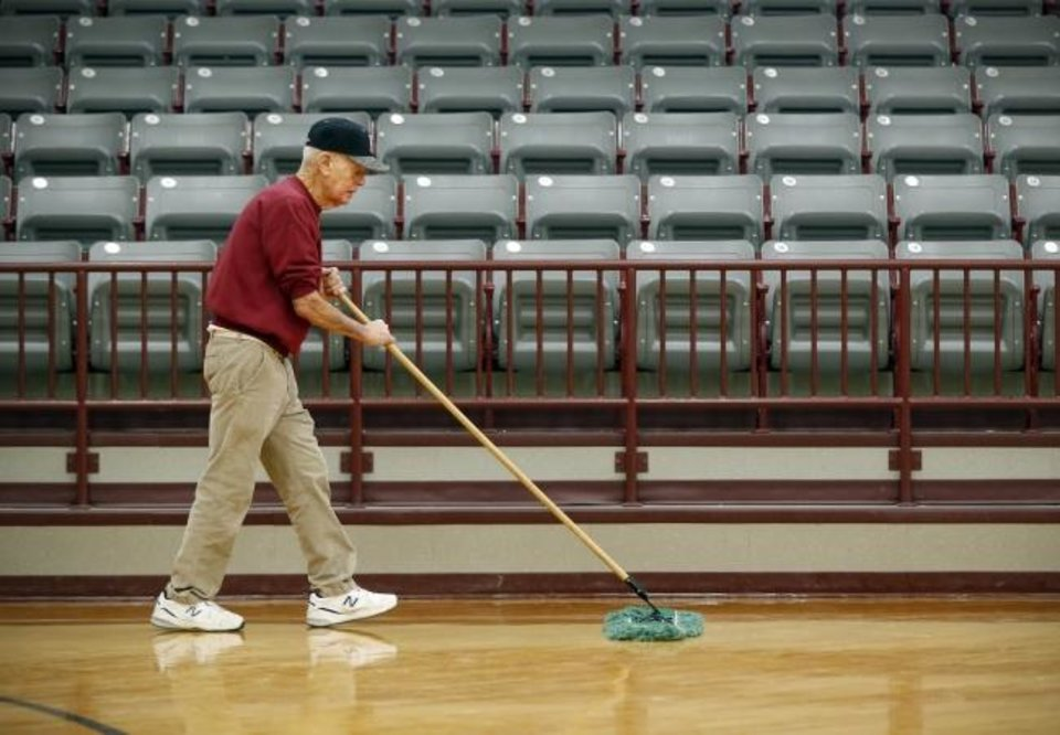 Photo -  Coach Joe Gilbert sweeps the floor before girls basketball practice in the gym inside Barnsdall High School in Barnsdall, Okla., Tuesday, Feb. 18, 2020. Gilbert has coached at Barnsdall and been sweeping this floor since 1954. [Nate Billings/The Oklahoman]