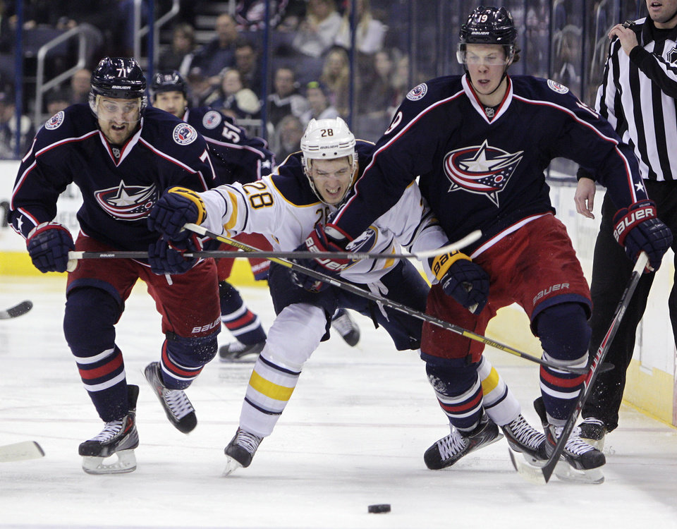 Photo - Columbus Blue Jackets' Nick Foligno, left, Ryan Johansen, right, and Buffalo Sabres' Zemgus Girgensons, of Latvia, chase a loose puck during the second period of an NHL hockey game, Saturday, Jan. 25, 2014, in Columbus, Ohio. (AP Photo/Jay LaPrete)