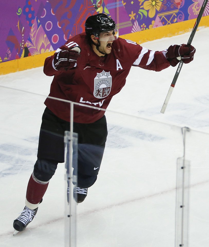 Photo - Latvia forward Lauris Darzins reacts after scoring a goal against Canada during the first period of a men's quarterfinal ice hockey game at the 2014 Winter Olympics, Wednesday, Feb. 19, 2014, in Sochi, Russia. (AP Photo/Mark Humphrey)