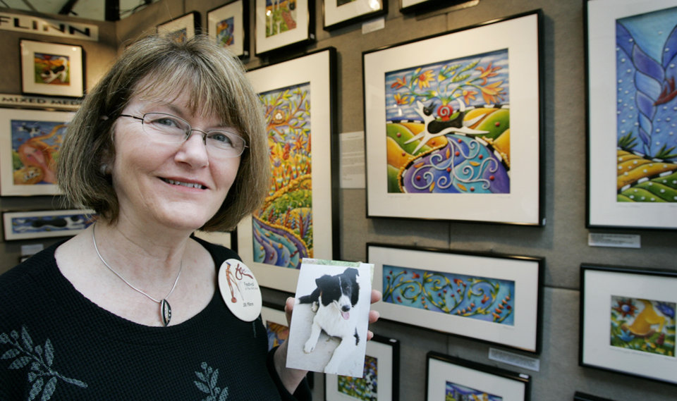"Jill Flinn of Glasgow, Mo. in her booth at the Festival of the Arts Wed. April 23, 2008 in downtown OKC. She bases some of her art on photographs of her pets. She is holding a photo of Mackenzie, a border collie mix, she based the work to the right ""Dogs Deliver Joy"" on. BY JACONNA AGUIRRE/THE OKLAHOMAN."