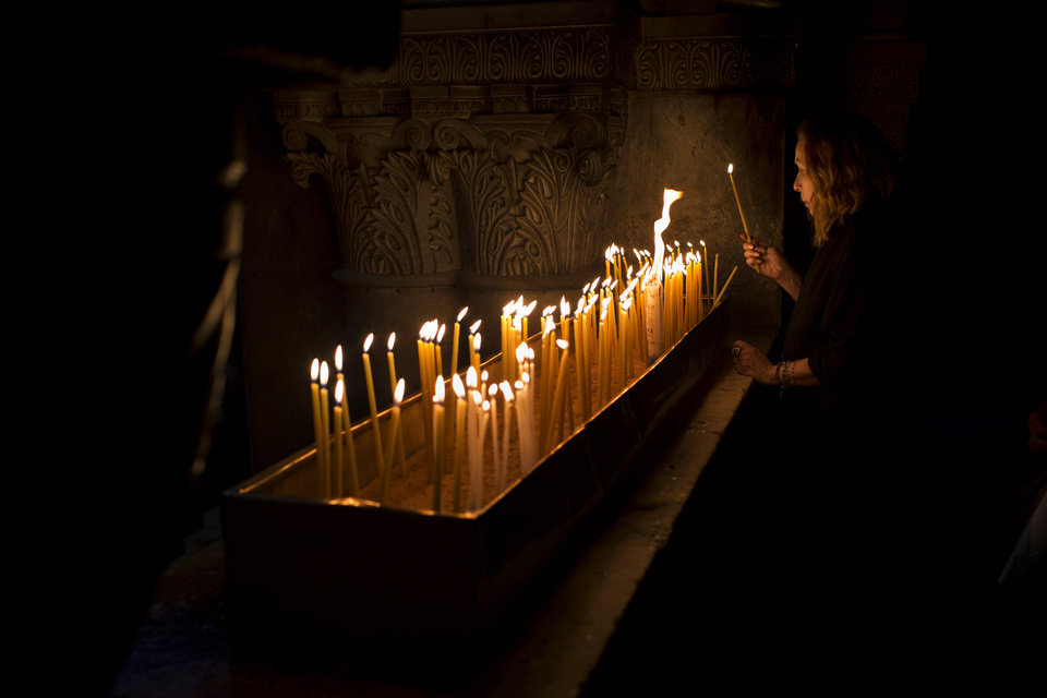 A Christian Catholic pilgrim lights a candle inside the Church of the Holy Sepulcher, traditionally believed to be the site of the crucifixion of Christ, in Jerusalem's Old City, Friday, March 29, 2013. Less than 2 percent of the population of Israel and the Palestinian territories is Christian, mostly split between Catholicism and Orthodox streams of Christianity. Christians in the West Bank wanting to attend services in Jerusalem must obtain permission from Israeli authorities. Israel's Tourism Ministry said it expects some 150,000 visitors in Israel during Easter week and the Jewish festival of Passover, which coincide this year. (AP Photo/Bernat Armangue)