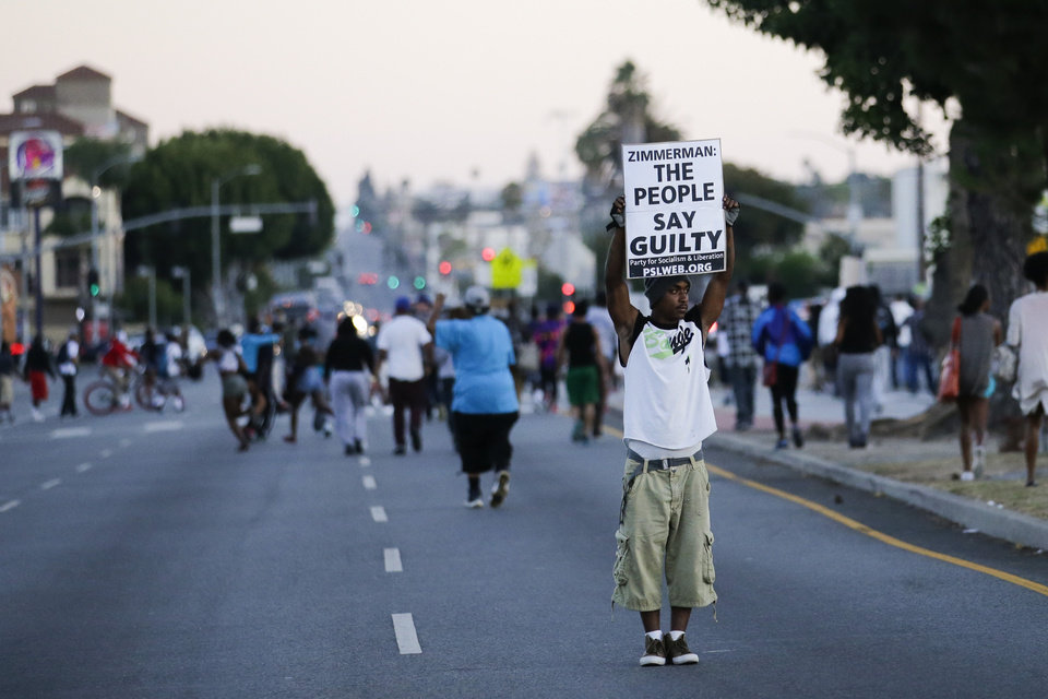 Photo - A protester holds up a sign while marching down the street during a demonstration in reaction to the acquittal of neighborhood watch volunteer George Zimmerman on Monday, July 15, 2013, in Los Angeles. Anger over the acquittal of a U.S. neighborhood watch volunteer who shot dead an unarmed black teenager continued Monday, with civil rights leaders saying mostly peaceful protests will continue this weekend with vigils in dozens of cities. (AP Photo/Jae C. Hong)