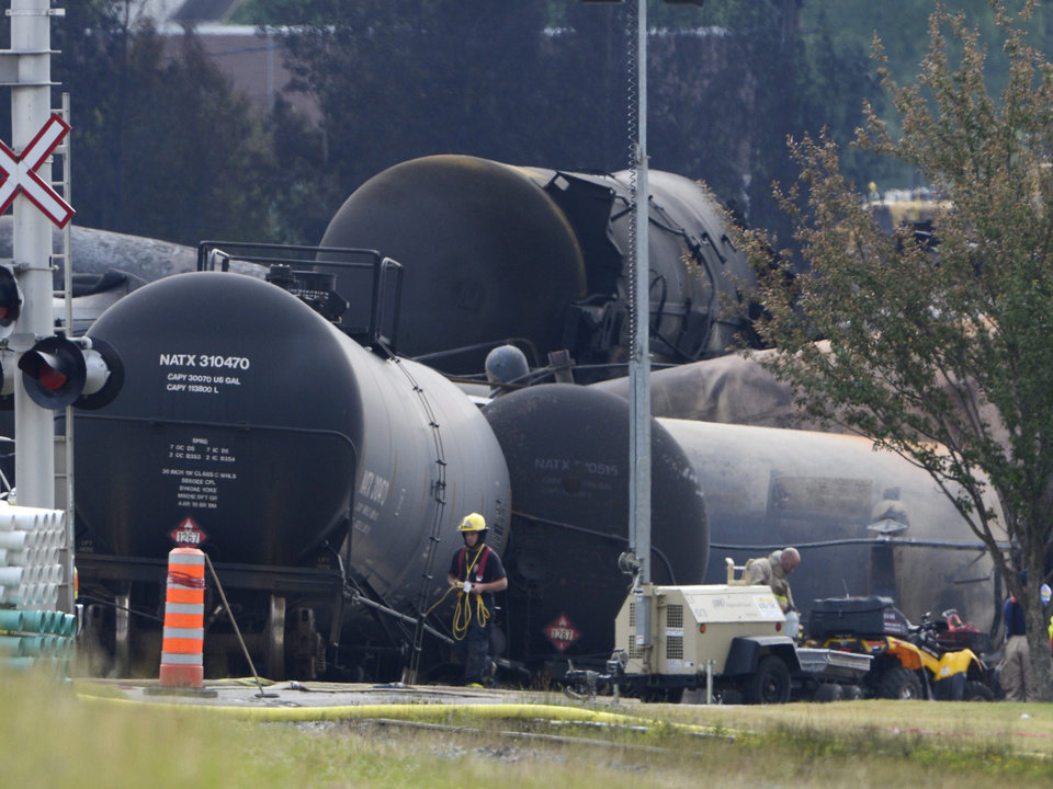 Photo - Cleanup continues at the scene of the Lac-Megantic, Quebec, runaway oil train derailment and explosion, Tuesday, July 9, 2013. Investigators looking for the cause of the fiery oil train derailment are zeroing in on whether an earlier blaze on the same train may have set off a chain of events that led to the explosions that killed at least 13 people. (AP Photo/The Canadian Press, Ryan Remiorz)