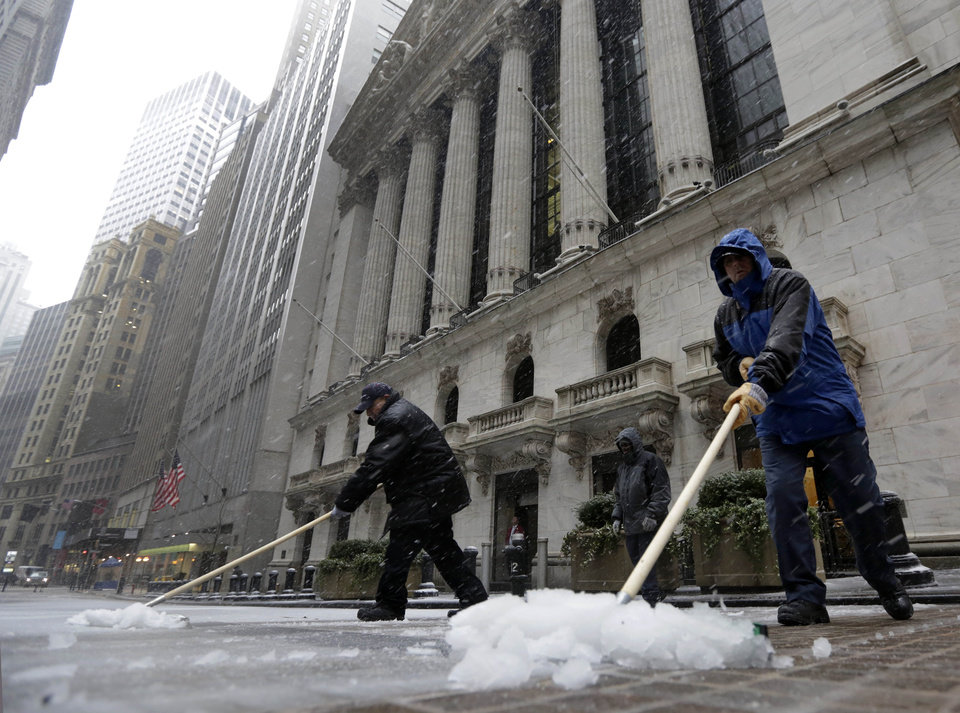 Workers clear snow in front of the New York Stock Exchange, Friday, Feb. 8, 2013. With a dangerous blizzard threatening the nation's biggest city with 50-mph gusts and more than a foot of snow, New Yorkers scrambled Friday to stock up on supplies and hunker down. (AP Photo/Richard Drew) ORG XMIT: NYRD119