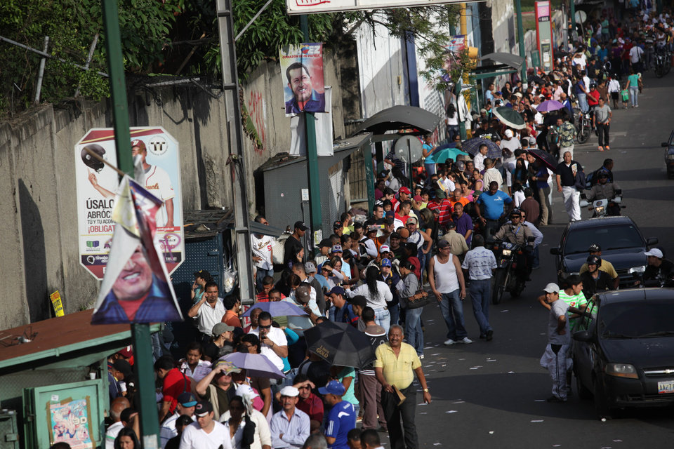 Photo -   Residents wait in line at a polling station to vote in the presidential election in the Catia neighborhood of Caracas, Venezuela, Sunday, Oct. 7, 2012. President Hugo Chavez is running against opposition candidate Henrique Capriles. (AP Photo/Rodrigo Abd)