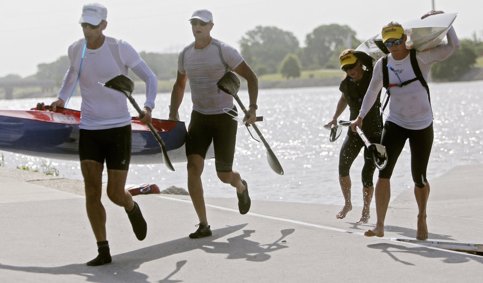 Photo - Male pair John Baltzell (far left) and Johan Dahl (middle, left) and female pair  Maggie Hogan (far right) and Kaitlyn McElroy (middle, right) carry their canoes across the dock during a portage section of the USA Canoe Marathon National Championships on the Oklahoma River in Oklahoma City on Sunday, June 22,  2014.  Photo by KT King, The Oklahoman