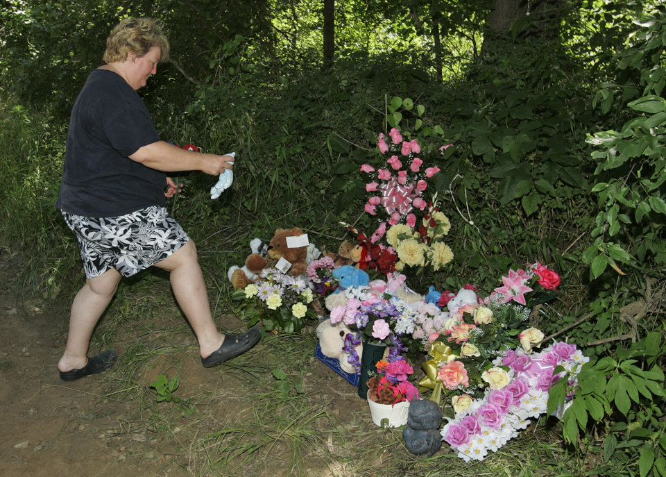 Photo - Teresa Williams brings a stuffed bear to a memorial on the side of the road for Skyla Whitaker and Taylor Paschal-Placker, Wednesday, June 11, 2008. The girls were found murdered Sunday night. (AP Photo)