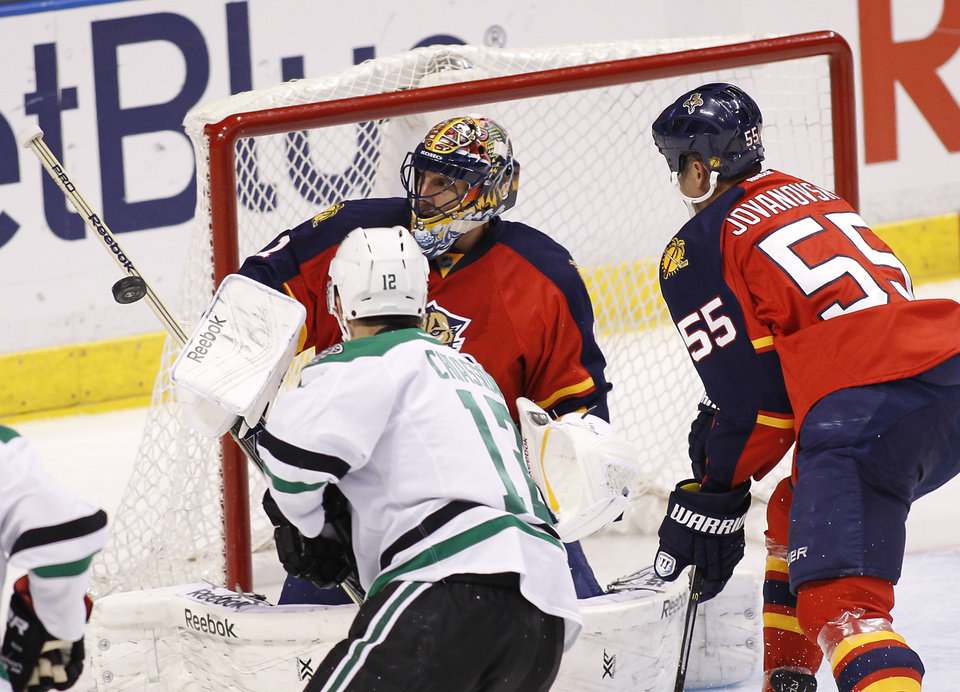 Photo - Florida Panthers goalie Roberto Luongo (1) blocks a shot as teammate  Ed Jovanovski (55) helps defend during the second period of an NHL hockey game against the Dallas Stars in Sunrise, Fla., Sunday, April 6, 2014. (AP Photo/Terry Renna)