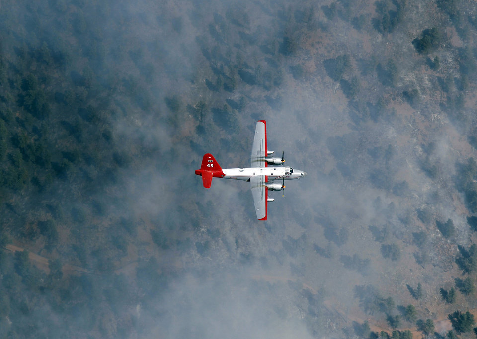 Photo -   In this aerial photograph, a slurry bomber passes through clouds of smoke on the way to making a drop on a ridge as the Lower North Fork Wildfire burns near the foothills community of Conifer, Colo., southwest of Denver on Tuesday, March 27, 2012. Firefighters are now able to actively battle the blaze on the ground that started on Monday and has already destroyed at least 16 homes in the rugged terrain. (AP Photo/David Zalubowski)