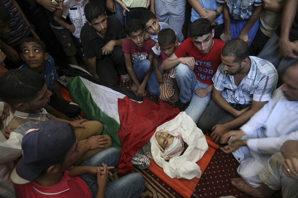 Photo - Palestinian relatives mourn over the body of Noor Alnajedy, 10,  who was killed during an Israeli air strike on a building near his family house, at the main mosque during his funeral in Rafah refugee camp, southern Gaza Strip, Friday July 11, 2014. Israel launched the Gaza offensive to stop incessant rocket fire that erupted after three Israeli teenagers were kidnapped and killed in the West Bank and a Palestinian teenager was abducted and burned to death in an apparent reprisal attack. The military says it has hit more than 1,100 targets already, mostly what it identified as rocket-launching sites, bombarding the territory on average every five minutes. (AP Photo/Eyad Baba)