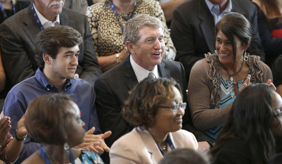 Photo - Bill Elliott, center, smiles with son Chase Elliott, left, and wife, Cindy, right, after being named as one of five inductees into the NASCAR Hall of Fame class of 2015, in Charlotte, N.C., Wednesday, May 21, 2014. (AP Photo/Chuck Burton)