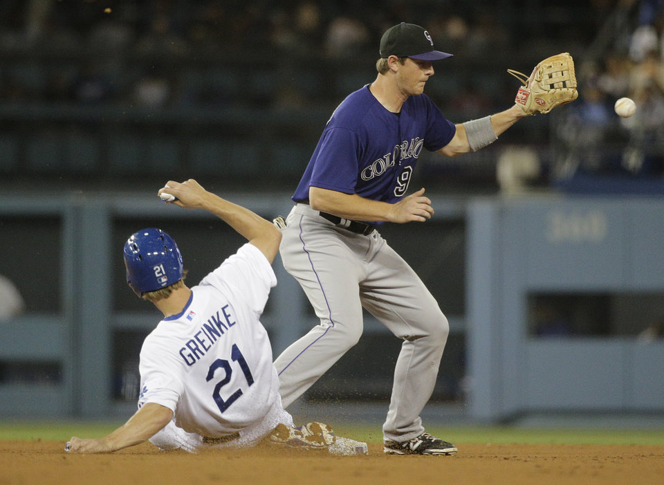 Photo - Los Angeles Dodgers starting pitcher Zack Greinke, left, takes second base on a fly ball hit by Hanley Ramirez as Colorado Rockies second baseman D.J. LeMahieu looks to fields the throw during the fifth inning of a baseball game on Tuesday, June 17, 2014, in Los Angeles. (AP Photo/Jae C. Hong)