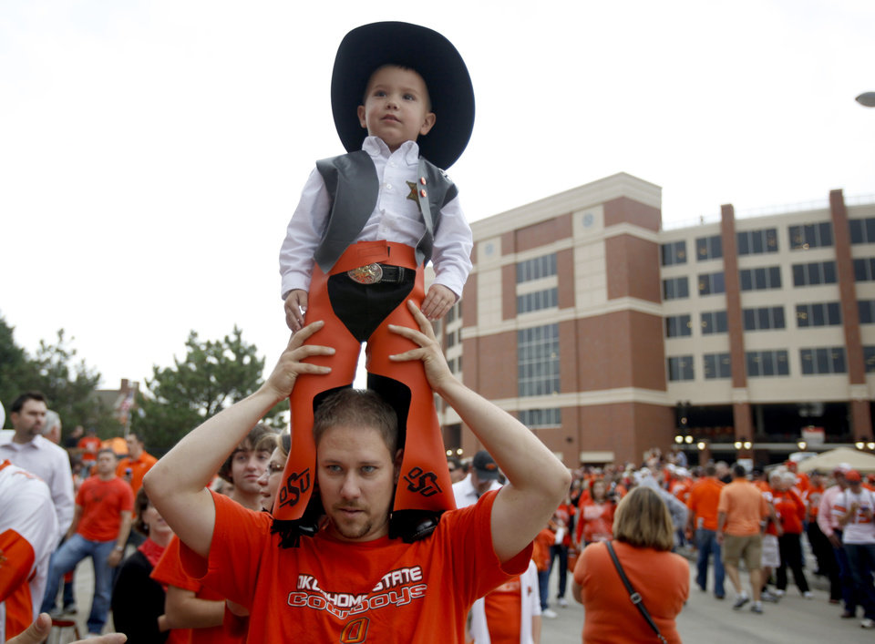 Photo - Matt White holds his son, Trent, 3, during  the Spirit Walk before the college football game between the Oklahoma State Cowboys (OSU) and the Nebraska Huskers (NU) at Boone Pickens Stadium in Stillwater, Okla., Saturday, Oct. 23, 2010. Photo by Sarah Phipps, The Oklahoman