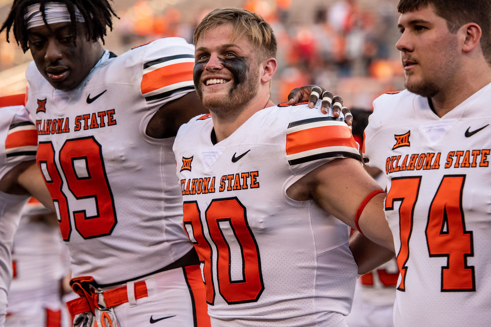 Photo - Sep 26, 2020; Stillwater, Oklahoma, USA; Oklahoma State Cowboys cornerback Braden Cassity (90) smiles with teammates after the game against the West Virginia Mountaineers at Boone Pickens Stadium. Mandatory Credit: Rob Ferguson-USA TODAY Sports