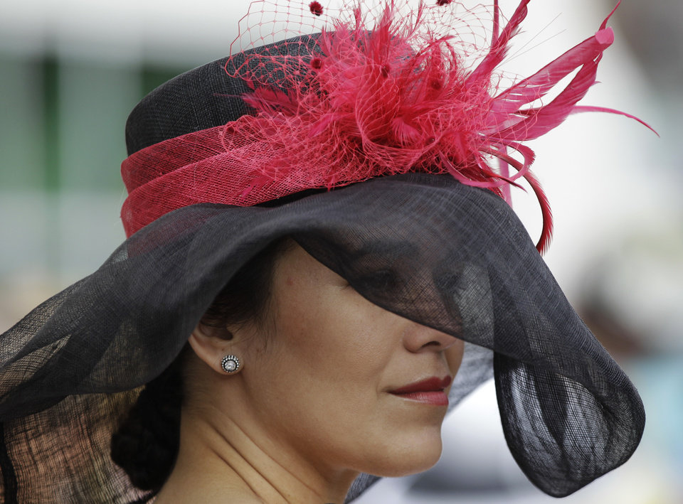 Photo - Jackie Resillez, from Cincinnati, waits for the start of the 138th Kentucky Derby horse race at Churchill Downs Saturday, May 5, 2012, in Louisville, Ky. (AP Photo/Mark Humphrey)  ORG XMIT: DBY115