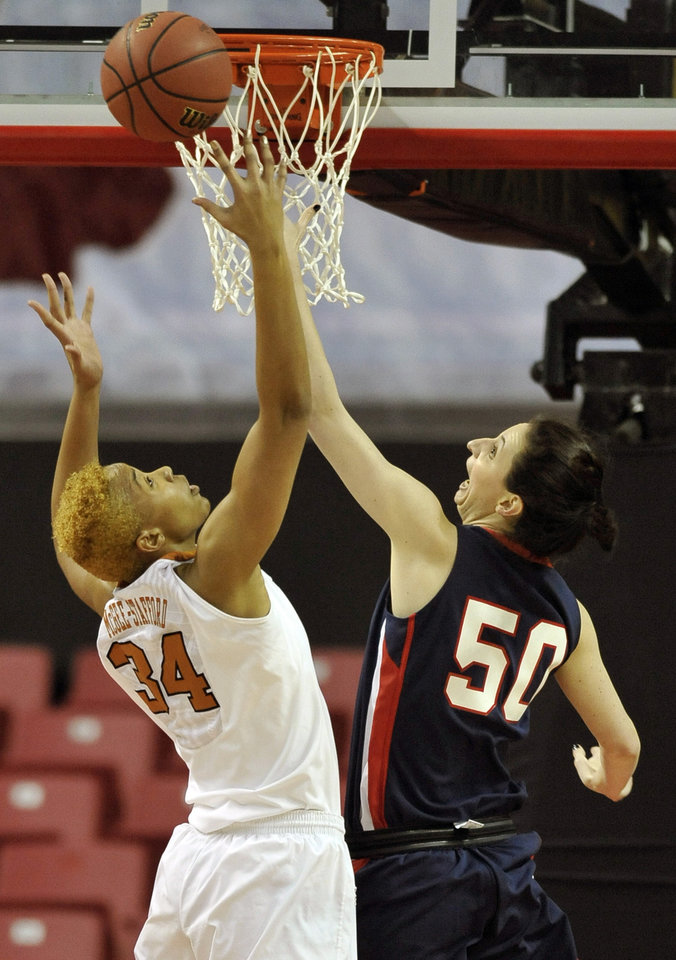 Photo - Penn's Courtney Wilson, left, and Texas' Imani McGee-Stafford both go for a rebound during the first half of the first round of the NCAA women's college basketball tournament on Sunday, March 23, 2014, in College Park, Md. (AP Photo/Gail Burton)