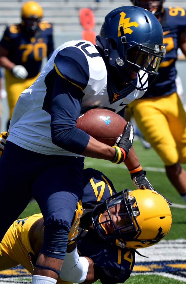 Photo - West Virginia's Jordan Thompson (10) is brought down by Ricky Rumph (14) during their  spring NCAA college football game in Morgantown, W.Va., Saturday, April 12, 2014. (AP Photo/Craig Cunningham)