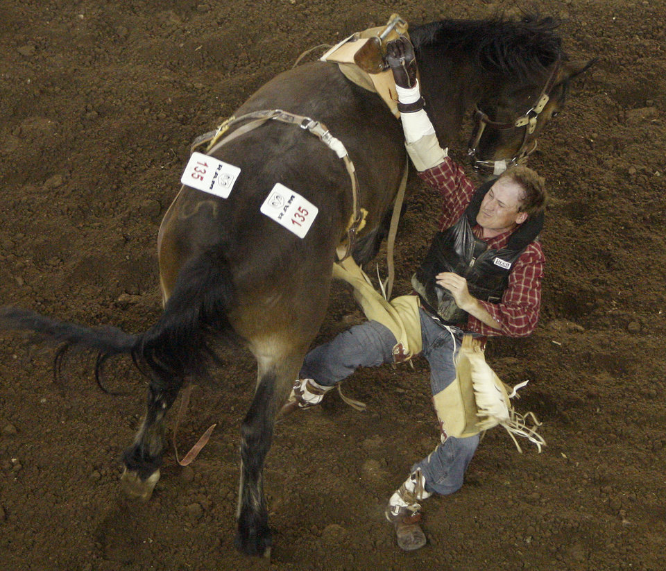 Brandon Holmes of Eva, Ala., falls of  during the bareback riding competition in the PRCA National Circuit Finals Rodeo at the State Fair Arena on Friday, March 30, 2012. Photo by Bryan Terry, The Oklahoman